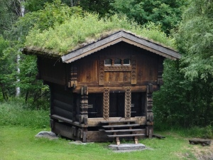 This is a Stabbur, a traditional Norwegian Storehouse. The 4 corners are typically raised by free-standing piles of stone and air underneath the floor to keep mice away and provide filtration for what is stored: milk, meat, grains, etc. This one is converted into a lodge - complete with a turf roof!